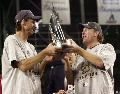 Arizona Diamondbacks pitcher Randy Johnson, left, and Curt Schilling, right, hold the World Series MVP trophy they will share after being named co-receipiants of the World Series Most Valuable Player award after the Diamondbacks beat the New York Yankees 3-2 in Game 7 of the World Series Sunday, Nov. 4, 2001, at Bank One Ballpark in Phoenix. (AP Photo/David J. Phillip)